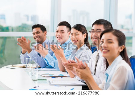 Smiling business people applauding at the conference - stock photo