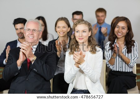 Smiling business people applauding to speaker after presentation
