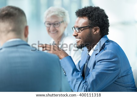 Smiling business people at meeting in office - stock photo