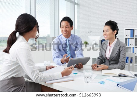 Smiling business people discussing idea on tablet computer