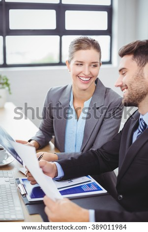 Smiling business people discussing over documents at computer desk in office