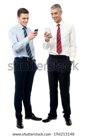 Smiling business people exchanging their mobile numbers - stock photo