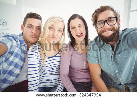 Smiling business people gesturing while taking selfie in office - stock photo