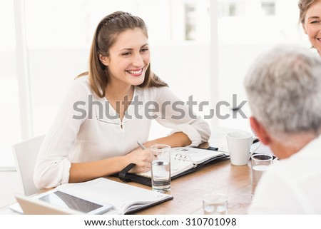 Smiling business people having a meeting in the office - stock photo