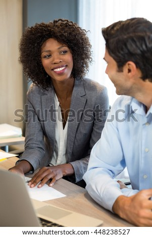Smiling business people interacting with each other in office