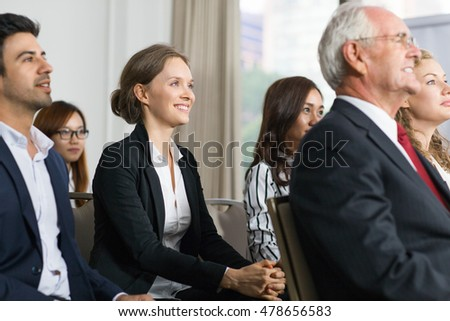 Smiling business people listening to speaker with interest