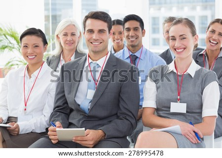 Smiling business people looking at camera during meeting in office - stock photo