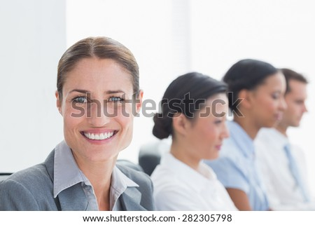 Smiling business people looking at camera in office