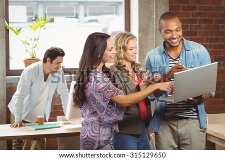 Smiling business people pointing towards laptop in creative office