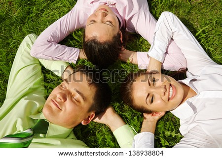 Smiling business people resting on grass