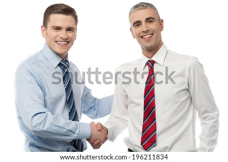 Smiling business people shaking hands over a deal - stock photo