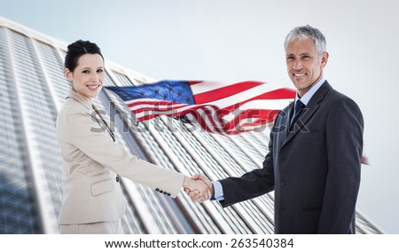 Smiling business people shaking hands while looking at the camera against american flag and skyscraper - stock photo