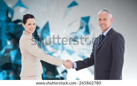 Smiling business people shaking hands while looking at the camera against angular design - stock photo