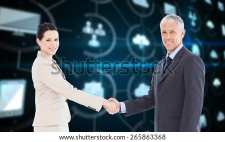 Smiling business people shaking hands while looking at the camera against apps interface - stock photo