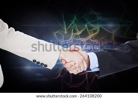 Smiling business people shaking hands while looking at the camera against black background with spark - stock photo