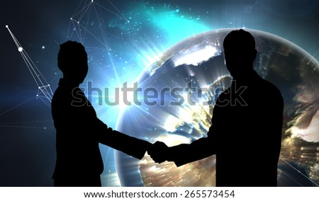 Smiling business people shaking hands while looking at the camera against earth seen from space - stock photo