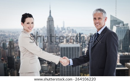 Smiling business people shaking hands while looking at the camera against new york - stock photo