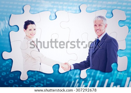 Smiling business people shaking hands while looking at the camera against stocks and shares - stock photo