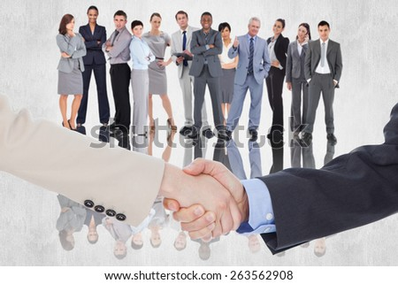 Smiling business people shaking hands while looking at the camera against white background - stock photo