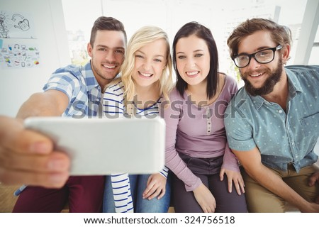 Smiling business people taking selfie on smartphone while sitting on desk in office - stock photo