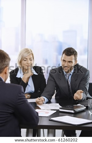 Smiling business people talking at meeting in office.?