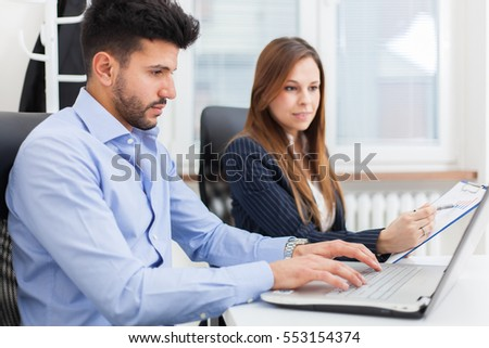 Smiling business people using a computer in their office