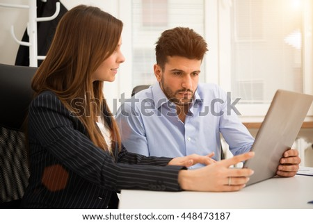 Smiling business people using a laptop computer in their office. Shallow depth of field, focus on the man. Controlled lens flare effect