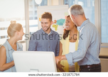 Smiling business people using computer in meeting room at creative office - stock photo