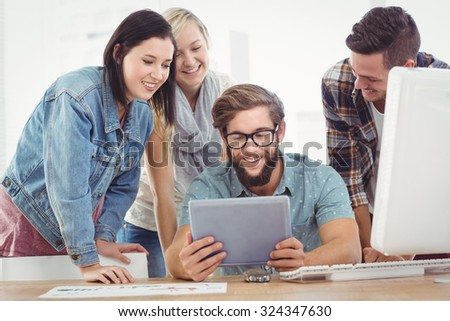 Smiling business people using digital tablet at computer desk in office - stock photo