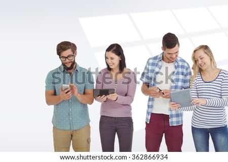 Smiling business people using electronic gadgets against grey vignette - stock photo