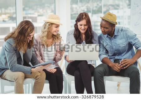 Smiling business people using technology while discussing in creative office - stock photo