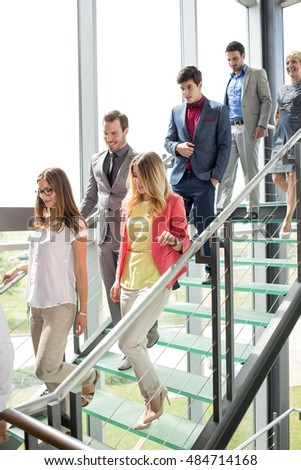 smiling business people walking down stairs in building