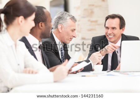 Smiling business people with paper work in board room - staff meeting - stock photo