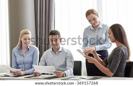 smiling business people with papers in office - stock photo