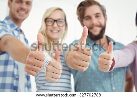 Smiling business people with thumbs up while standing at office - stock photo