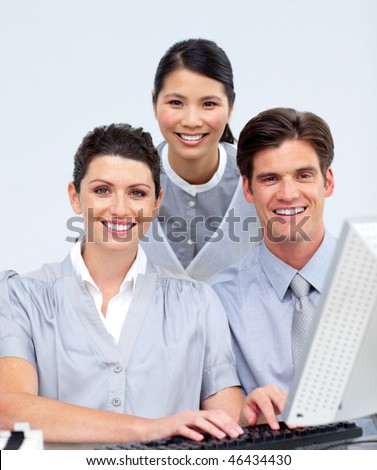 Smiling business people working at a computer in a company