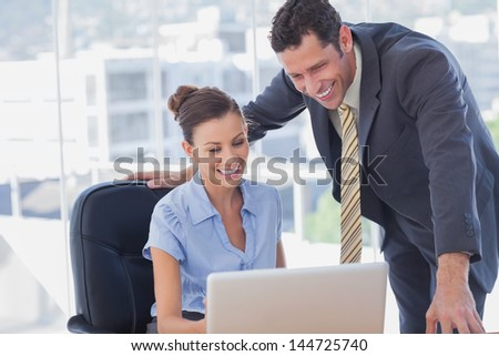 Smiling business people working together with the same laptop in the office - stock photo