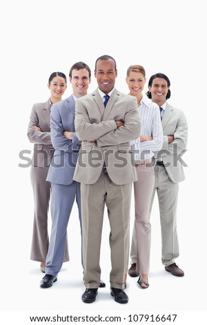 Smiling business team crossing their arms against white background