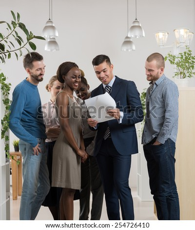 Smiling business team discussing documents and reports at office - stock photo