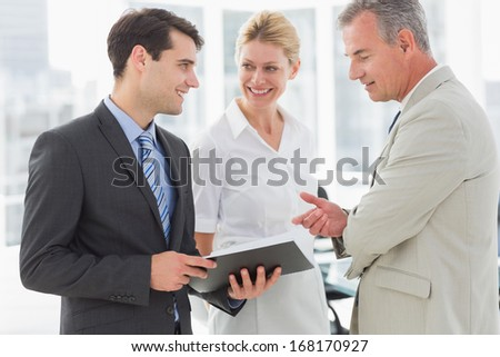 Smiling business team going over documents in the office