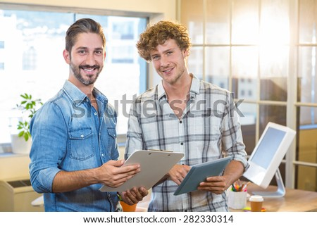 Smiling business team holding clipboard and tablet in the office