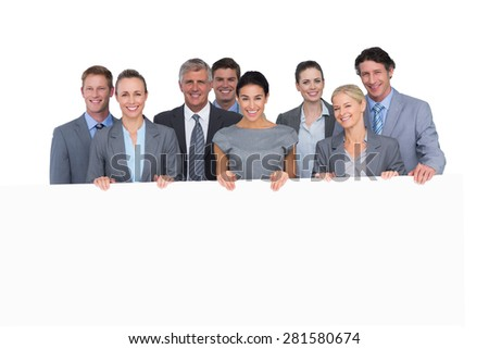 Smiling business team holding poster on white background - stock photo