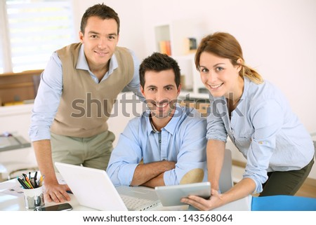 Smiling business team looking at camera - stock photo