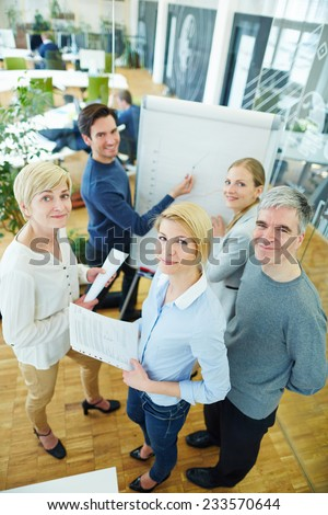 Smiling business team members in office in front of flipchart - stock photo