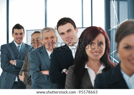 Smiling business team standing in a row at office