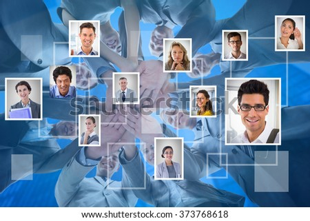 Smiling business team standing in circle hands together against blue background