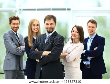 Smiling business team standing upright with their hands on their - stock photo