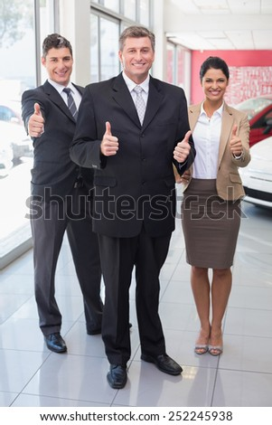 Smiling business team standing while giving thumbs up at new car showroom - stock photo
