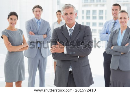 Smiling business team standing with arms crossed in the office - stock photo