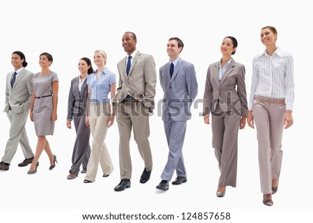 Smiling business team walking against white background - stock photo